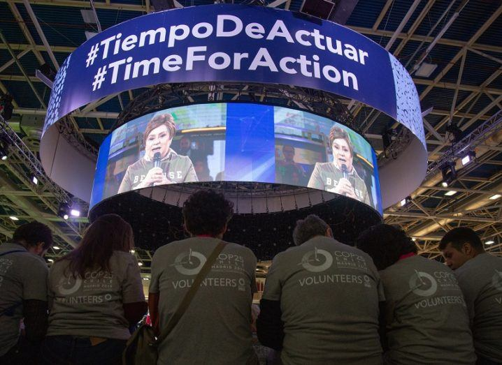 Patricia Espinosa, executive secretary of UN Climate Change, appearing on a big screen while COP25 volunteers sit and look on.