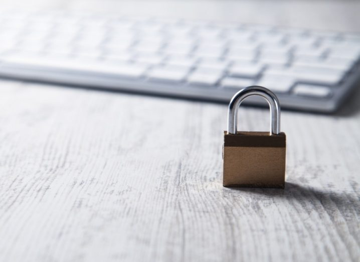 Padlock with computer keyboard in background symbolising cybersecurity.