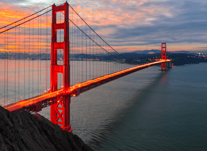 A large, red cable bridge across the San Francisco Bay Area.