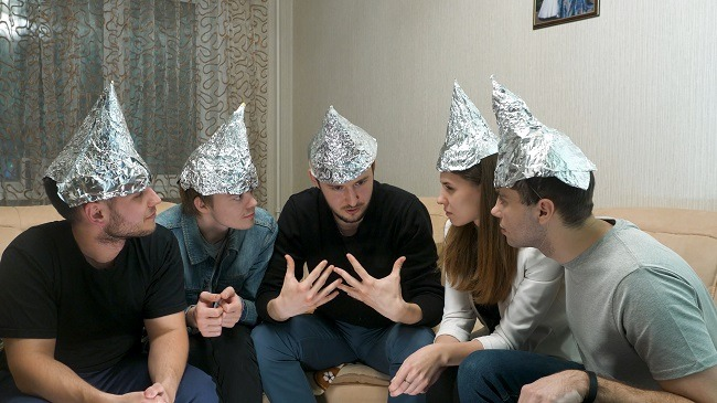 Group of people wearing tinfoil hats leaning in close to one another in a living room.