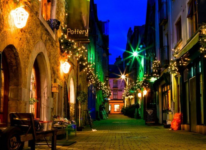 Old Galway city street at night with lamps illuminating the pathway.