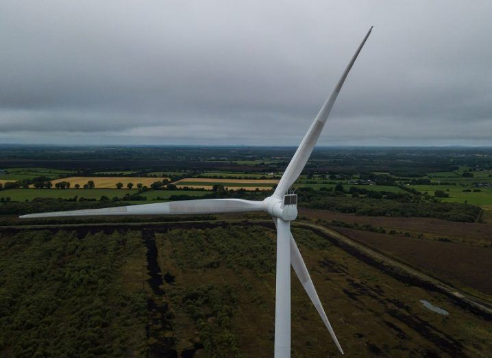 Close-up aerial view of a wind turbine against a grey sky background.