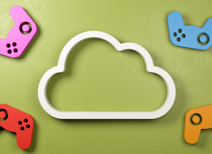 A green background with a white, wooden cloud on it, surrounded by pink, blue, red and orange console controllers also made out of wood.