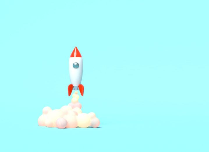 A cartoon rocket ship blasting off above a cloud of smoke on a turquoise background.
