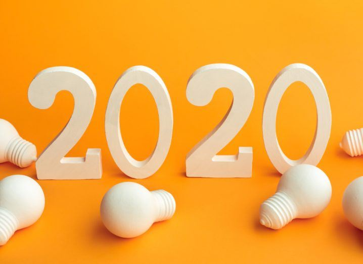 3D white wooden numbers reading '2020' surrounded by a scattering of white wooden models of lightbulbs on a crisp orange background.
