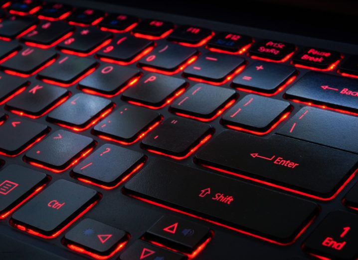 View of black keyboard keys backlit with red bright light.
