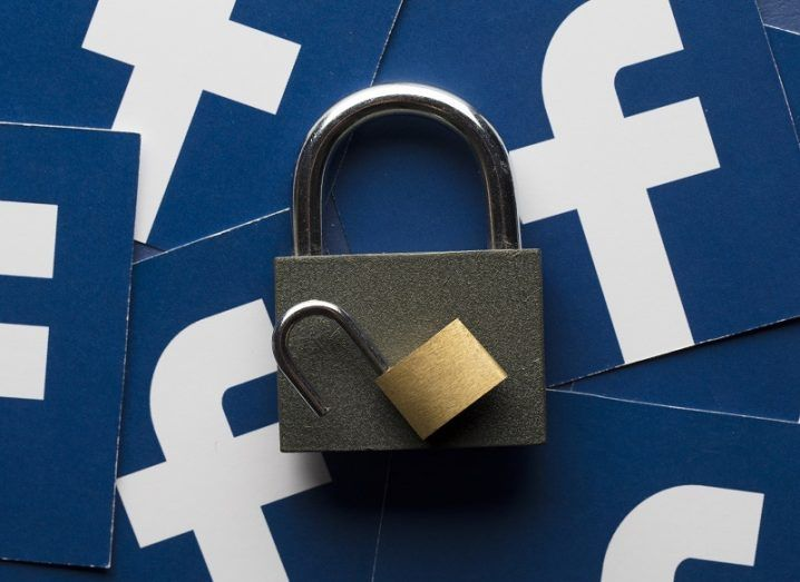 A large and small padlock on top of a pile of cards with Facebook logos.