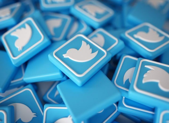 Pile of 3D blue Twitter logos with white birds on them.