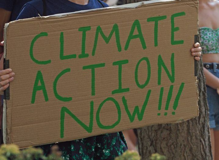 Close up of a person holding a sign that reads, 'Climate action now'.