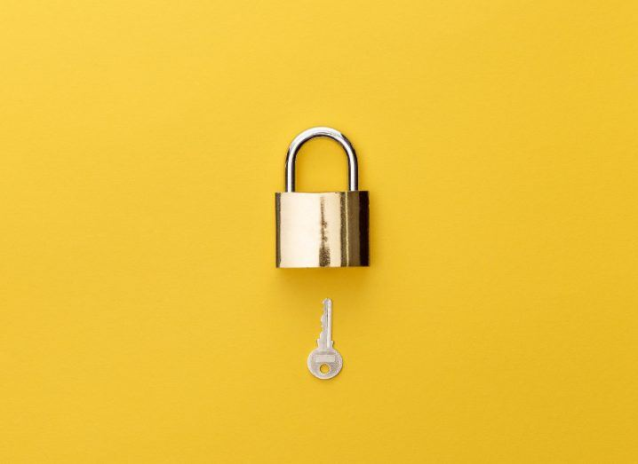 Overhead view of padlock and key on yellow background.