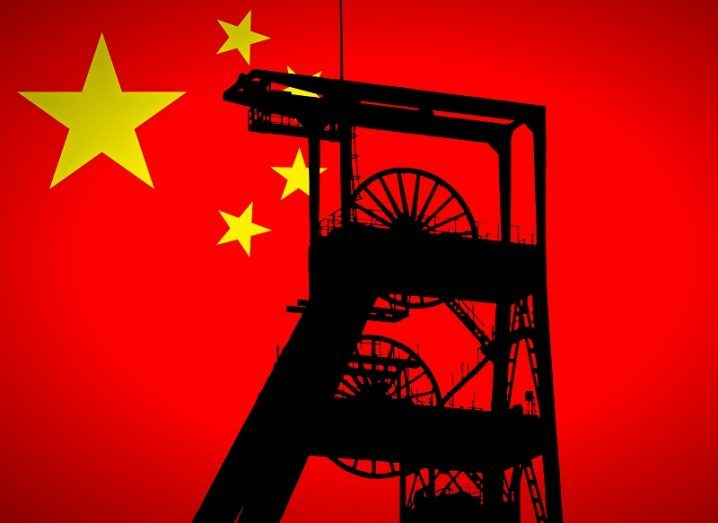 Concept shot of a silhouette of a coal mining wheel against the Chinese flag.