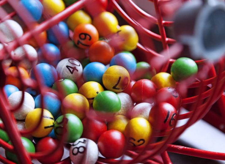 Close-up of a red-wire lottery drum filled with colourful numbered balls.