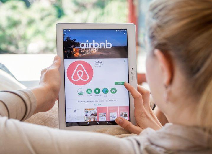 Person sitting on a couch looking at the Airbnb app on a tablet.