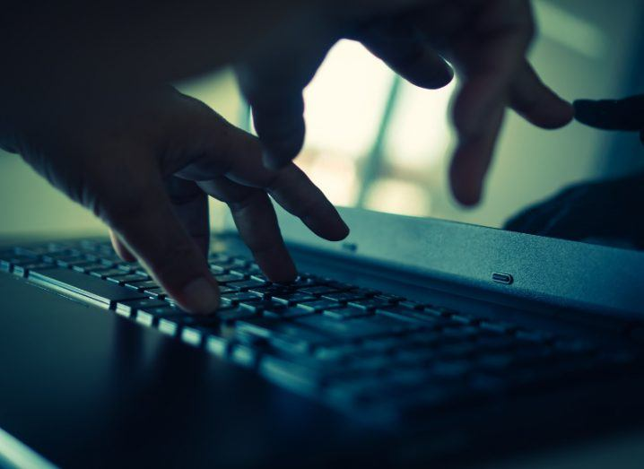 View of pair of hands typing on keyboard of dark-coloured laptop in dimly lit shadowy room.