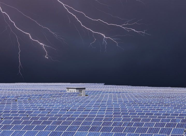 A field of solar panels with dark, stormy skies in the background.