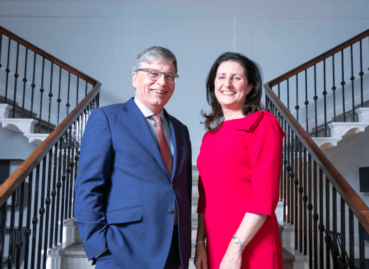 The CEO of Arkphire wears a navy suit and stands on a set of stairs. He is wearing glasses and has grey hair. Beside him is the founder of Trilogy Technologies, who is wearing a red dress. She has brown hair.