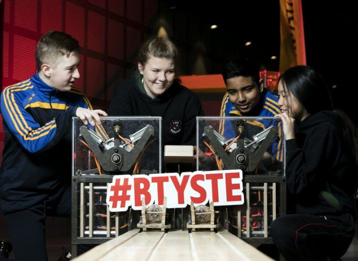 Four teenagers prepare to launch rockets made from plastic bottles and other materials on a track emblazoned with #BTYSTE.