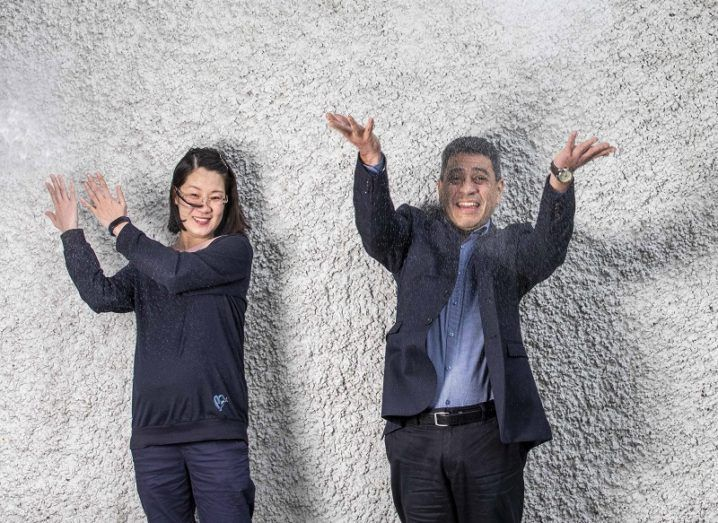 Dr Carlos Ochoa and Dr Yongli Yuan smiling and throwing salt in the air against a white pebbledash wall.