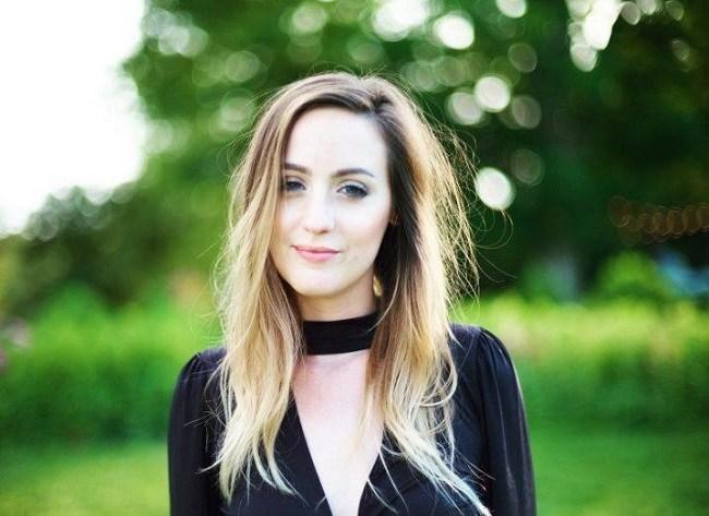 Caitlin Vander Weele in a black top wit black neckband, smiling, against a grassy background.