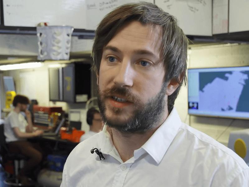 Conor McGinn in a white shirt in his robotics lab.