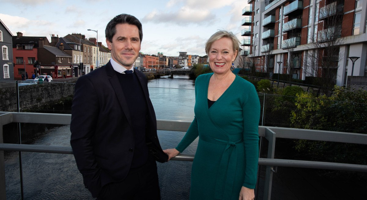A professional man and woman are standing outside in front of the river in Cork, smiling into the camera.