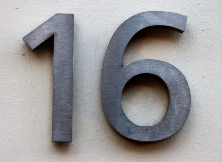 The number 16 in grey metal letters on a white wall.