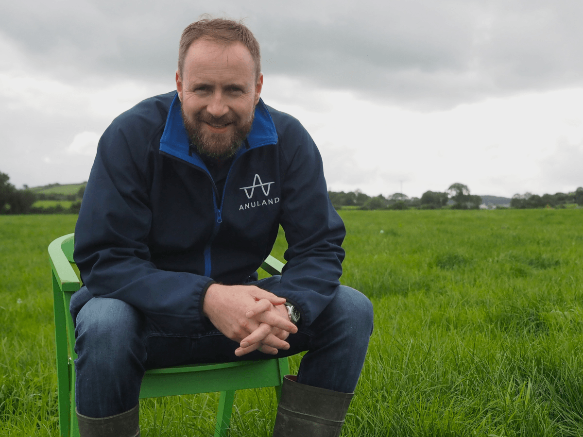 A bearded man with brown hair wearing a navy fleece and blue jeans with wellies sits on a green plastic charge in a large field full of grass.