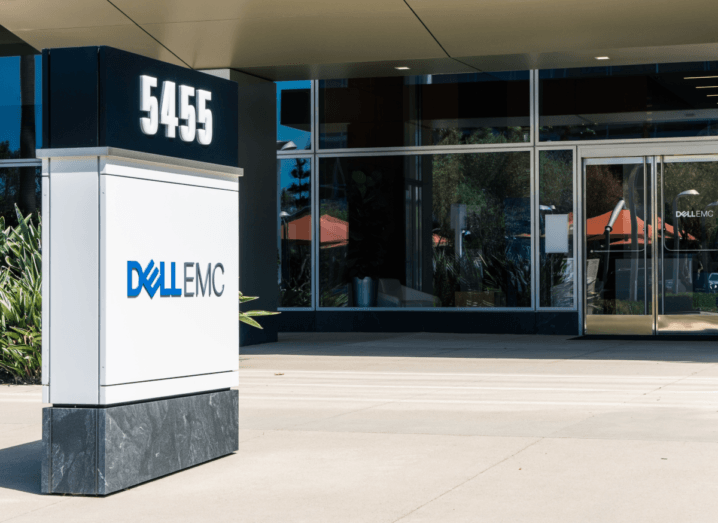The exterior of a Dell office building in Santa Clara. It has a glass front door and there is a large pillar with the Dell logo outside and some potted plants.
