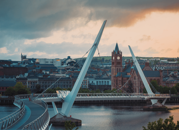 A twisty foot and bicycle bridge with large white monuments sticking out of it crossing a body of water in Derry.