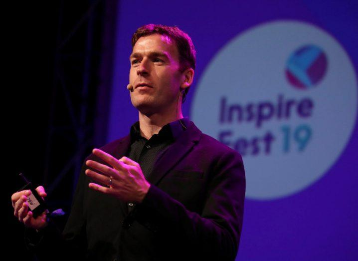 A man in a black suit stands on a stage with a purple screen in the background that reads 'Inspirefest 19'.