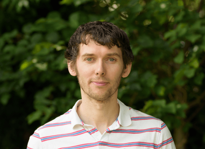 A man with brown hair and stubble wears a white polo shirt with red and blue stripes on it. He is standing in front of a bush.
