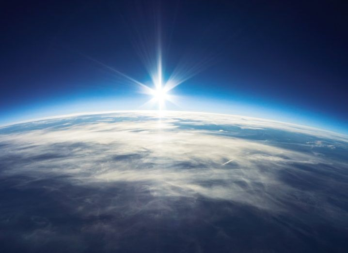 Earth's atmosphere in the foreground with the sun in the background.