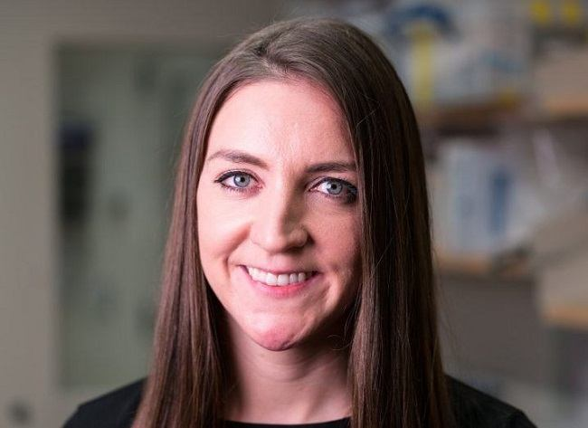 Headhsot of Dr Eimear Dolan smiling with her lab in the background.