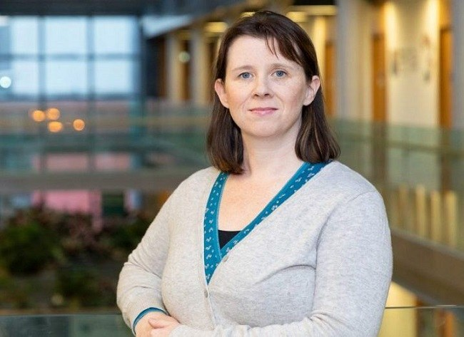 Dr Emma Whelan in a white cardigan and turquoise shirt with a large open building space in the background.