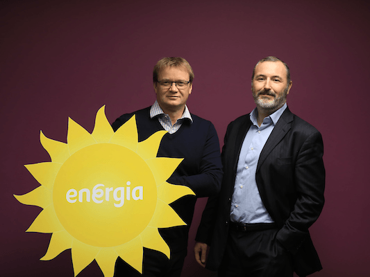 A man with a navy sweatshirt and white shirt underneath holds a big yellow cardboard sun that reads 'Energia'. He is standing beside a man in a black suit and blue shirt, in front of a burgundy wall.