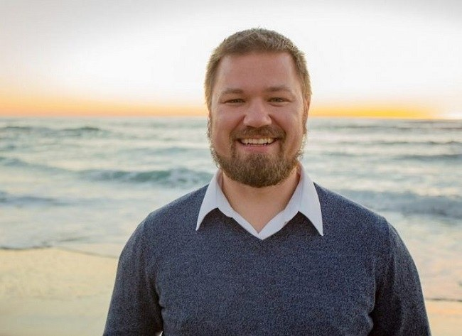 Erik Trask in a blue jumper and white shirt smiling against a sunset background by the sea.