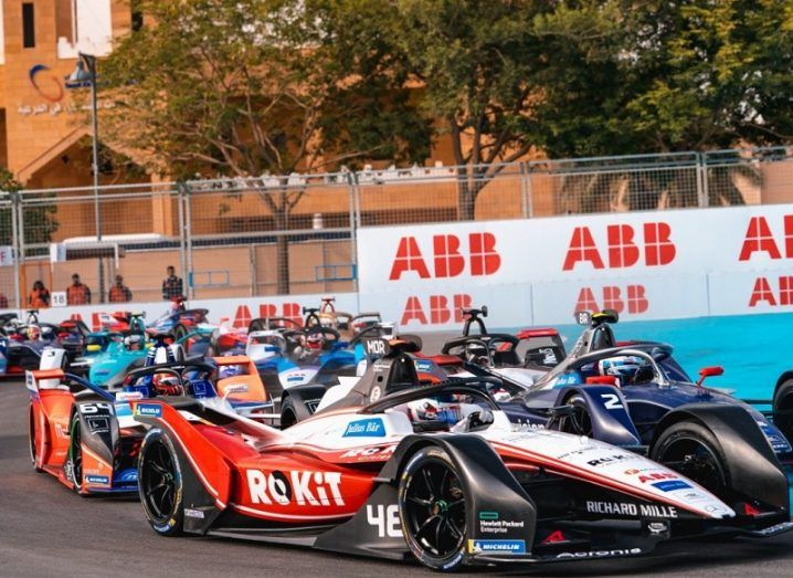 Formula E cars during a race bunched up together.