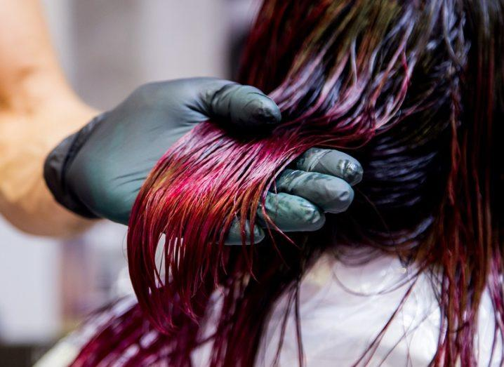 Black glove holding black hair being dyed red.