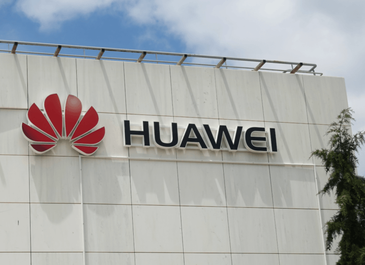 The Huawei logo on a white wall, under a blue sky with some clouds and a tree in the foreground.