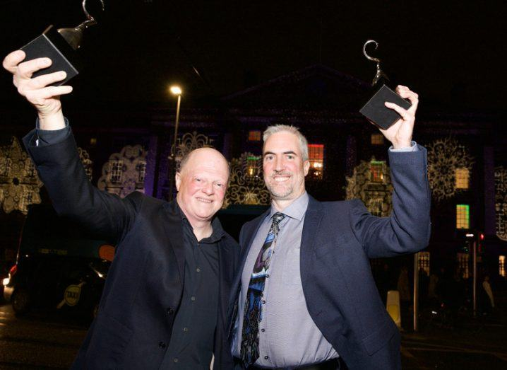 Two men in suits hold aloft their awards gongs in celebration against a dark night sky.