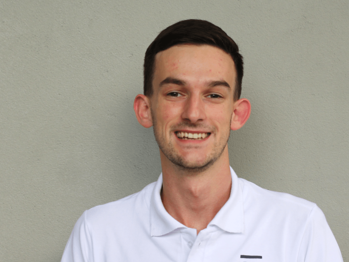 A young man with brown hair, wearing a white polo shirt smiles while standing in front of a beige wall.