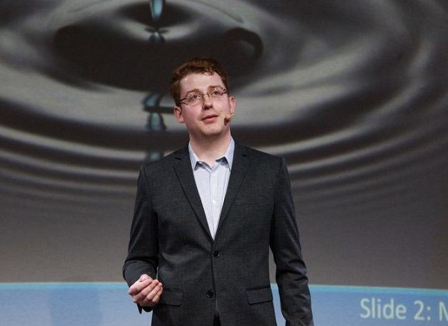 James Blackwell in a black blazer and white shirt speaking on a stage.