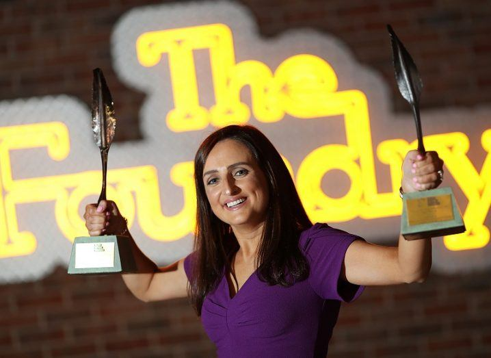 A woman in a purple dress stands holding an award in each hand in front of a neon sign that reads 'The Foundry'.