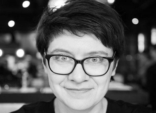 Black and white headshot of Dr Tanya Lokot wearing glasses.