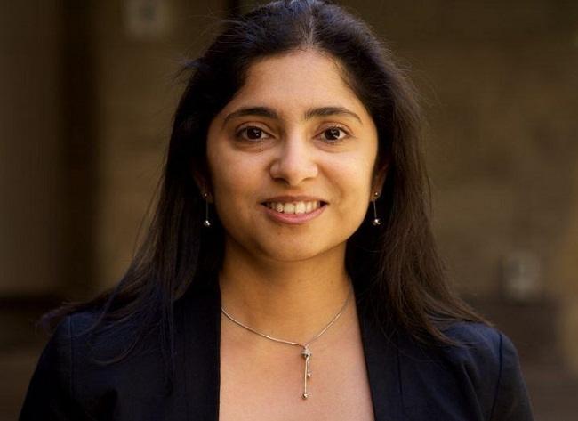 Headshot of Madhu Bhaskaran smiling in a black top against a red-brick wall background.