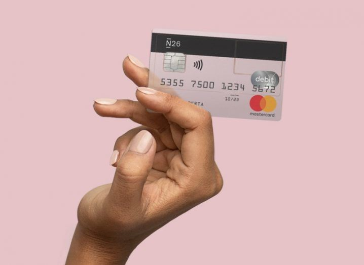 Hand holding an N26 debit card against a pink background.