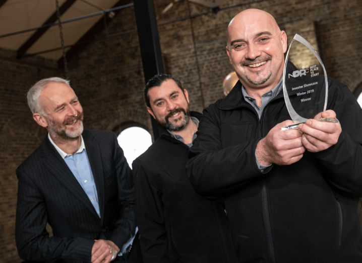 A man with grey hair and a beard wearing a black stripe suit smiles beside the Spire founders, who are both wearing black jackets with grey shirts underneath, one of which is holding a glass NDRC award.
