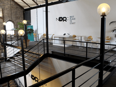 Dark brown floorboards and a staircase leading up to a balcony on which NDRC is located. The reception area has large potted plants, a large white wall that has the NDRC logo on it and a number of tables and chairs dotted around.