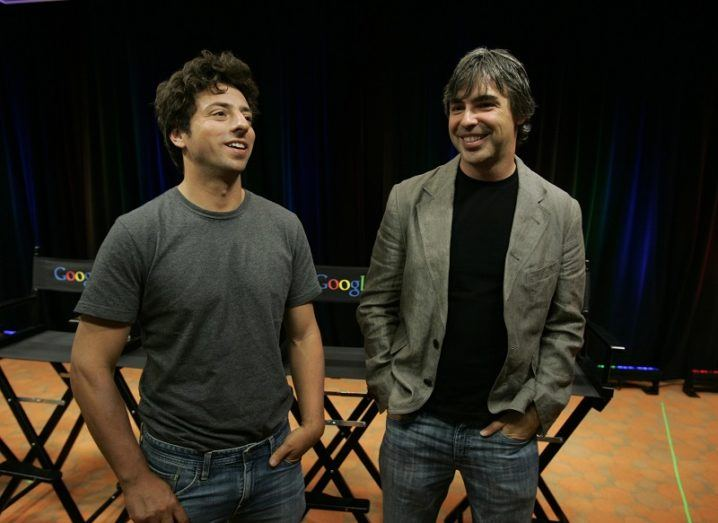 Sergey Brin and Larry Page standing beside each other smiling with fold-out chairs and a black curtain behind them.