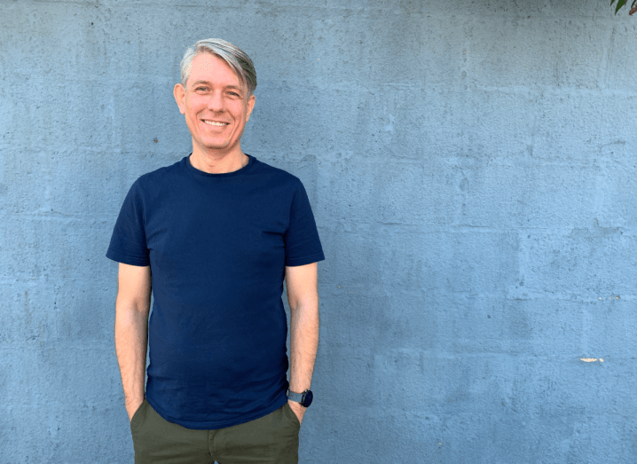 A man with grey hair with a side fringe stands in front of a blue wall. He is wearing a navy T-shirt and a smartwatch with a pair of dark green chinos.